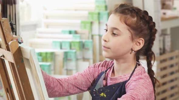 Thumbnail for Cute Little Girl Painting on Easel at School