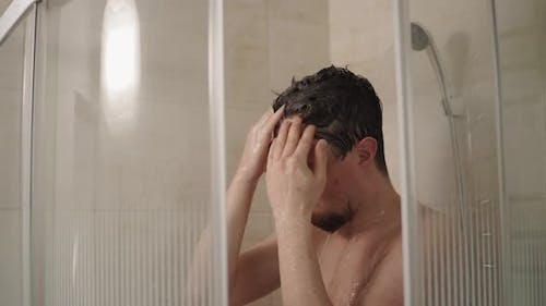 Brunet Man Is Washing Head in a Shower in Home, Close-up