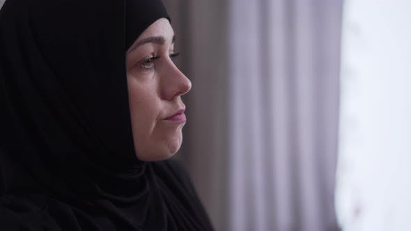 Thumbnail for Close-up Face of Beautiful Upset Woman in Hijab Looking Out the Window at Home. Portrait of Sad