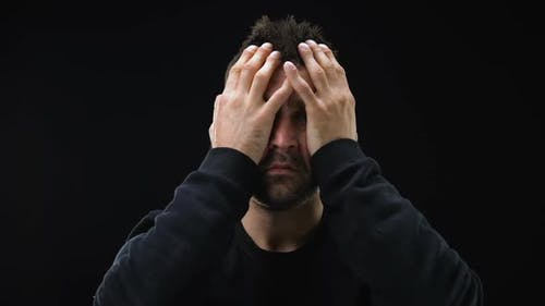 Desperate Criminal Repenting on Dark Background, Feeling Sorry, Mental Anguish