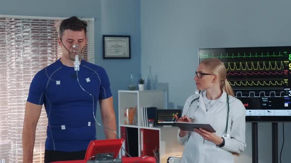 Thumbnail for Athlete in Oxygen Mask Doing Stress Test While Cardiologist with Tablet Monitoring His EKG