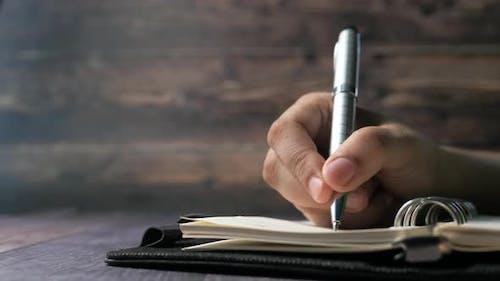 Close Up of Women Hand Writing Journal