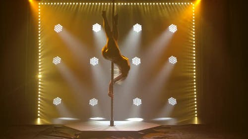 Young Woman Dancing on a Pole, Dancer, Fitness and Sport. Pole Dance. Silhouette of a Slender