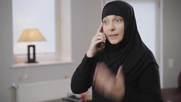 Thumbnail for Portrait of Young Modern Muslim Woman in Hijab Talking on Smartphone and Gesturing Emotionally