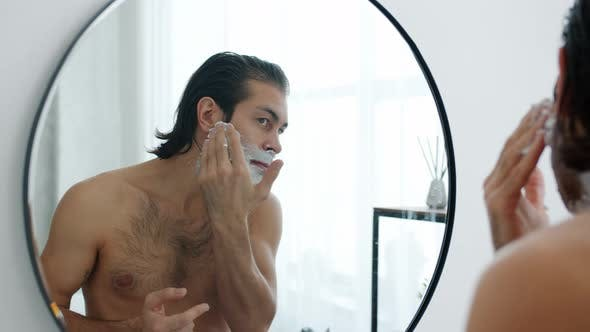 Topless Man Applying Shaving Cream on Stubble Looking at Mirror Reflection in Bathroom