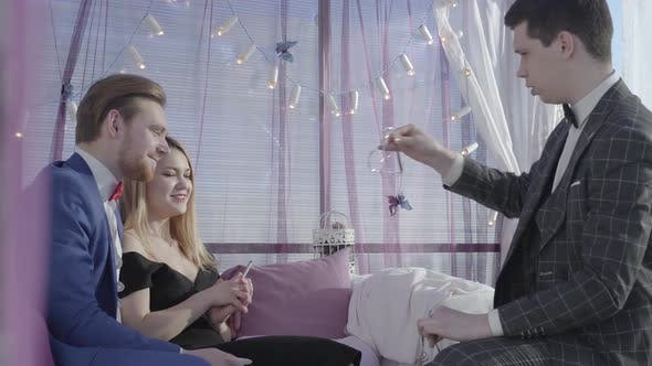 Cover Image for Happy Blond Couple Sit on the Sofa and Watching How Young Illusionist Show Them Magic Tricks with