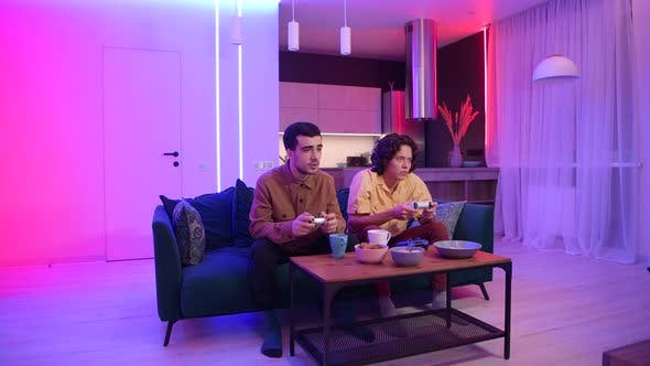 Thumbnail for Two Young Concentrated Men Playing Video Games While Sitting Sofa Neon Color Room