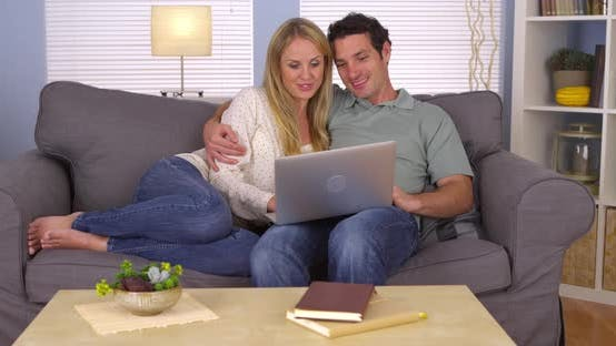 Thumbnail for Happy couple using laptop on couch