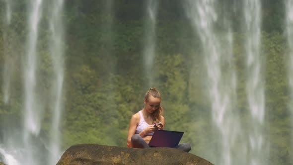 Thumbnail for Girl Sits with Laptop and Phone on Cliff at Water