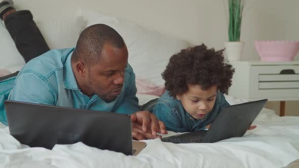 Cover Image for Caring Black Dad Teaching Son Using Laptop at Home