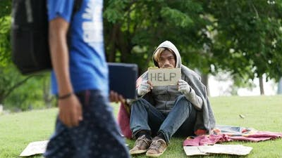 Homeless man sitting and holding help sign