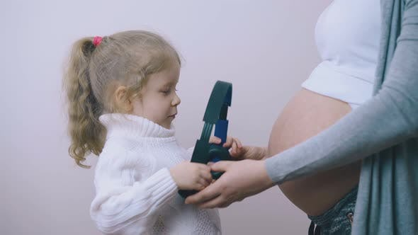 Little Girl Puts Headphones on Waist with Pregnant Mom Help