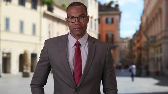 Successful African-American professional posing confidently in Italian street