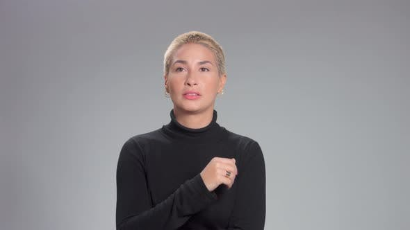 Blondine mit Kurzhaarschnitt in Studio-Posen für Kamera auf graue ideale Haut