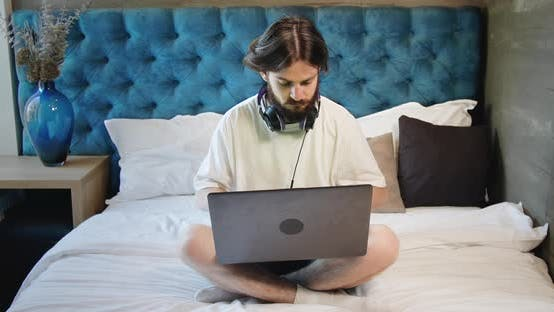 Freelancer Sitting on Bed with Laptop