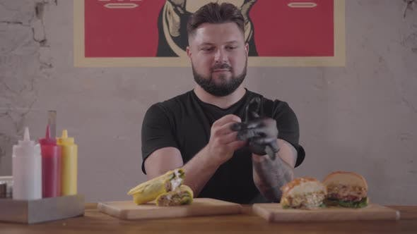 Thumbnail for Bearded Man Sitting at the Table in Front of Appetizing Burger and Shawarma Preparing for Eating