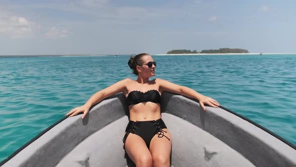 Young Woman in a Bikini and Sunglasses Lies on the Bow of Boat Floating By Ocean