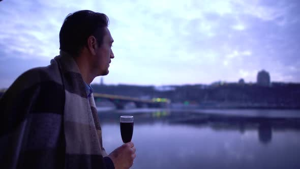 Thumbnail for Lonely Man in Blanket Standing Near the River and Drinking Alcohol