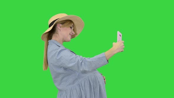 Thumbnail for Charming Pregnant Woman in a Hat Making Selfie on a Green Screen, Chroma Key