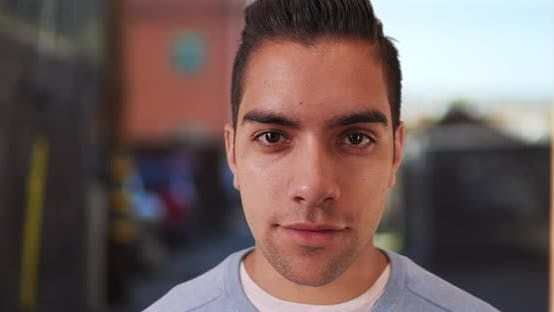 Thumbnail for Wide angle close up of handsome Latin male with undercut looking at camera