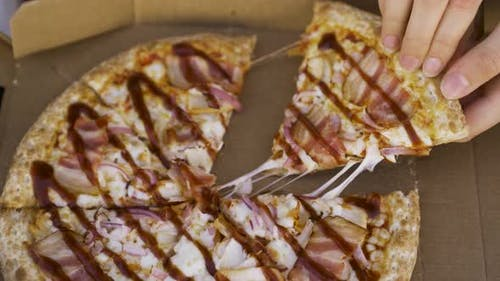 Taking slice of pizza with chicken and barbeque sauce