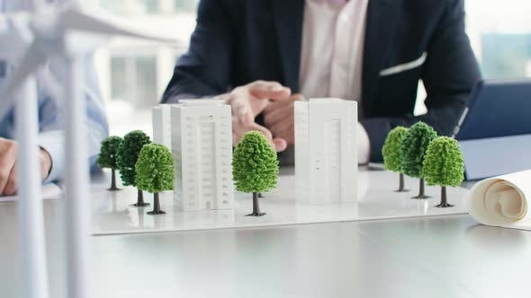 Professional coworkers over architectural model