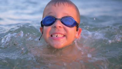 Cheerful boy in goggles bathing in the sea