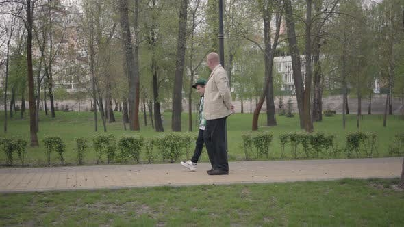 Thumbnail for Adorable Grandfather and Cute Little Grandson Walking in the Park Together