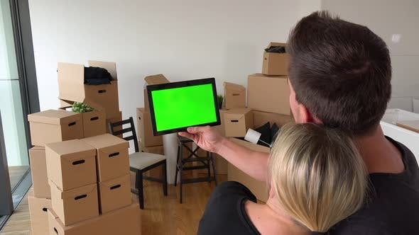 Thumbnail for A Moving Couple Looks at a Tablet with Green Screen in an Empty Apartment