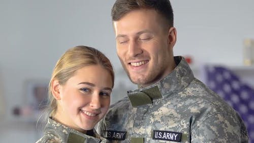 Happy Young Serviceman and Woman Looking Camera