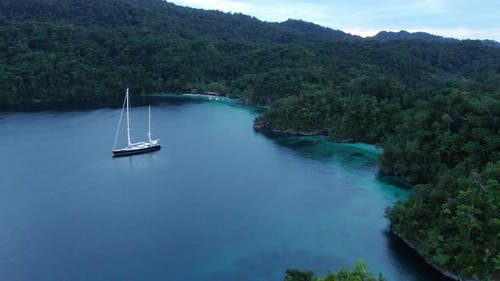 Aerial View Of Triton Bay: Boat On Turquoise Sea And Green Tropical Trees In Kaimana Islands