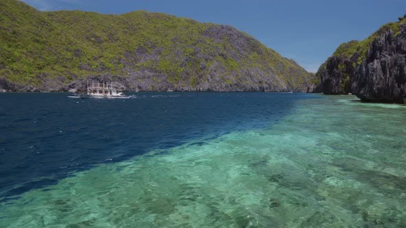 Tourist Island Hopping Boat in Ocean Strait with Rippled Surface. Matinloc Island. Tour C. Bacuit
