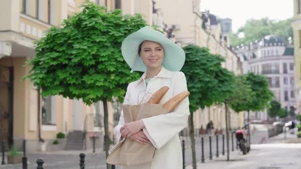Thumbnail for Stilvolle Dame in elegantem Hut stehend auf der City Street mit Baguettes. Französisch aussehende Mitte Erwachsene
