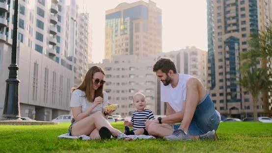 Thumbnail for Family Sitting on the Grass in the City Laughing with a Small Child