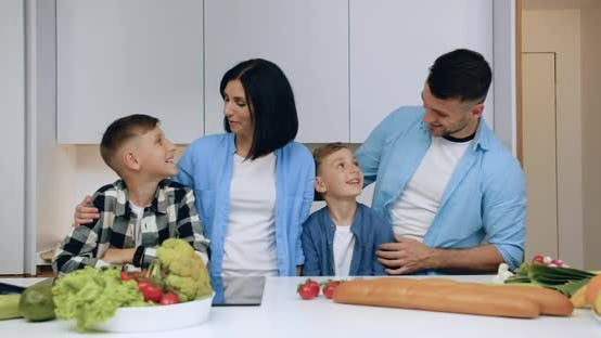 Thumbnail for Friendly Married Couple and Their Sons Posing on Camera in Beautiful Modern Kitchen