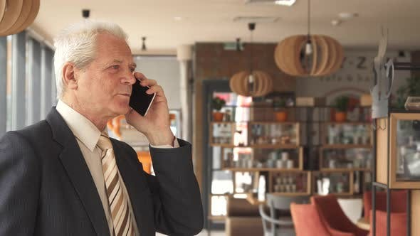 Thumbnail for Senior Businessman Fininshes To Talk on the Phone at the Cafe
