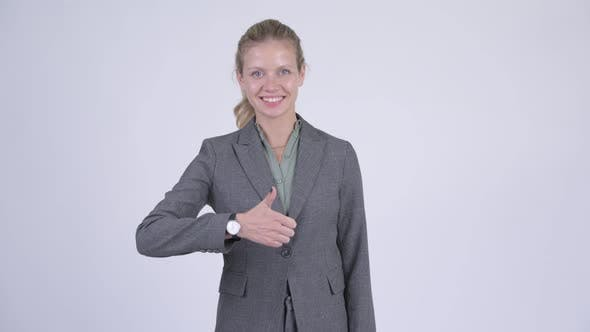 Cover Image for Young Happy Blonde Businesswoman Giving Thumbs Up