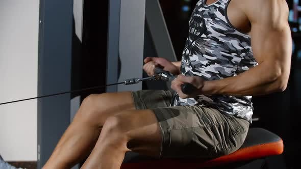 Cover Image for Attractive Man Training Strong Hands and Back Exercising on Rowing Sport Machine