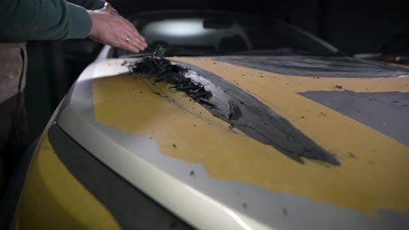 Designer Is Creating Billet of Details for Tuning Auto From Black Plasticine in Dark Garage Using