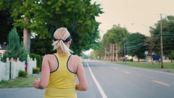 Thumbnail for A Young Woman Jogs Along a Typical US Suburb