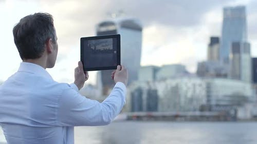 Business man takes a photo of the city scape and River Thames with his ipad/digital digital tablet