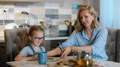Mom and Daughter Eat Dessert Food in Kitchen Rbbro