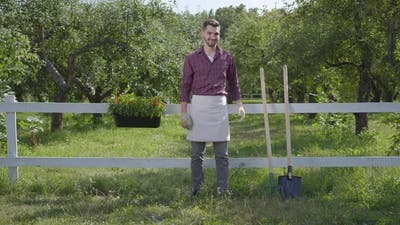 Professional Young Farmer in Garden Gloves Standing in the Green Summer Garden Near the Fence