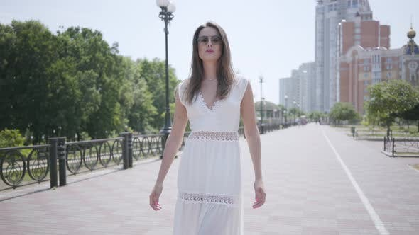 Thumbnail for Portrait Young Girl with Long Brunette Hair Wearing Sunglasses and a Long White Summer