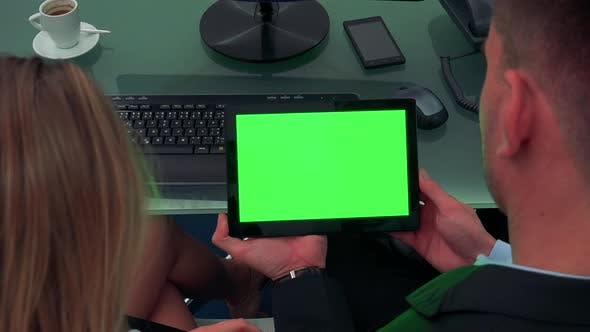 Thumbnail for A Man and a Woman Sit at a Desk in an Office and Look at a Tablet with a Green Screen