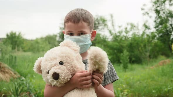 Little child in mask holding teddy bear and waving hand