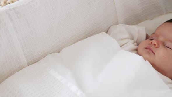 Thumbnail for Baby girl sleeping in bassinet