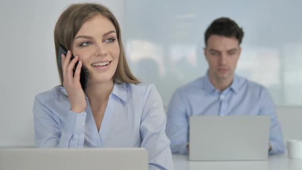 Thumbnail for Young Businesswoman Talking on Phone, Discussing Work