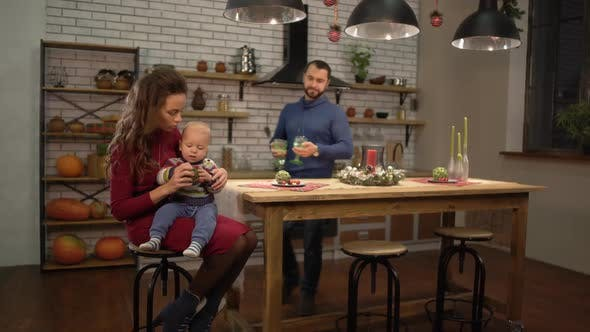 Thumbnail for Young Pretty Woman Sitting at the Table in the Kitchen with Baby on Her Pals While Handsome Bearded