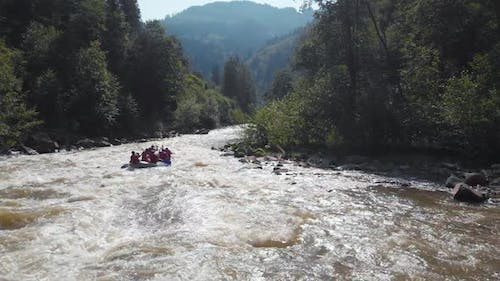 People Rafting on Mountain River Back View